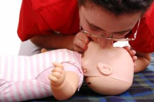 Practising CPR on a baby resuscitation manikin